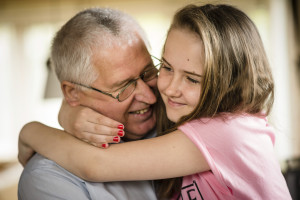 Authentic photo of happy grandfather hugging with his granddaughter indoor at home