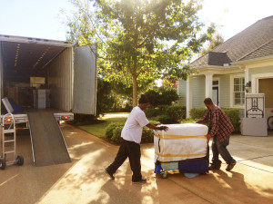 Two men unloading furniture from moving truck into home. Furniture is wrapped in furniture blankets and the truck is half way empty.